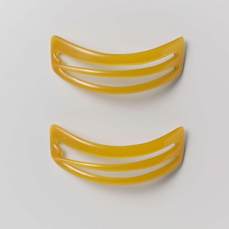 Anonymous | Haarspeld van oranjegele kunststof, in gebogen trapeziumvorm, Anonymous, c. 1875 - c. 1900 | Haarspeld van onversierde oranjegele kunststof, in gebogen trapeziumvorm, met drie horizontale balken, waarvan de middelste aan een kant los zit en de speld vormt.