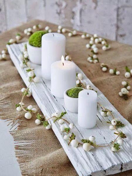 Centre de table pour la décoration : une planche récup peinte en blanc, de la mousse dans des petits vases blancs, des bougies blanches de différentes tailles