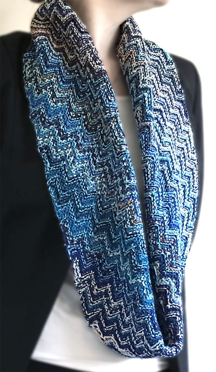 Free Knitting Pattern for Skein Hash Cowl - Infinity scarf designed to be knit with leftover stash and scrap yarn. Knit flat in a garter stitch chevron on the bias. Designed for fingering weight yarn but adaptable to other weights. Designed by Sybil R