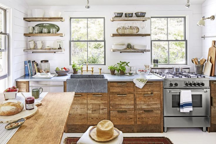 In a space-starved kitchen, it's tempting to go the all-white route, but this kitchen opts for a layered mix of materials, including reclaimed South Carolina barnwood (the cabinets and shelves), galvanized metal (the countertops), soapstone (the sink), and even unlacquered brass (the hardware).