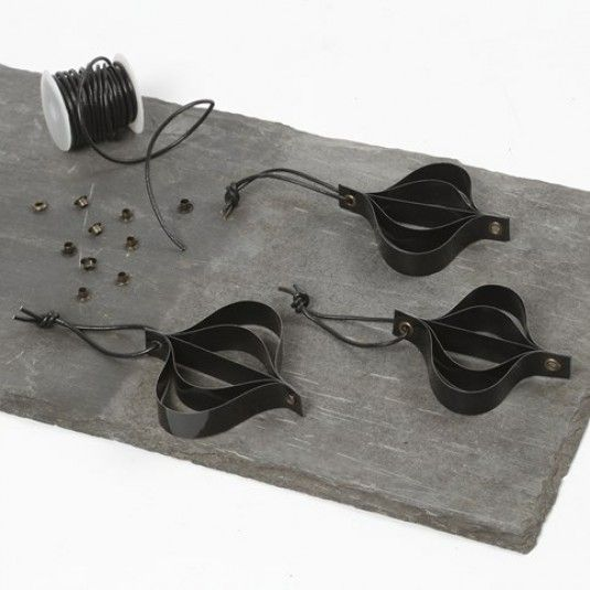 Dekoration av svarta lackstrimlor i öljett med lädersnöre