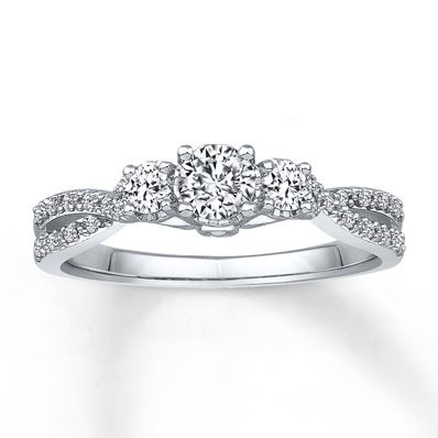 A round diamond nestled by two more diamonds forms the sparkling center of this pretty engagement ring for her. Intertwining waves of additional diamonds line the 14K white gold band to complement. The ring has a total diamond weight of 1/2 carat. Diamond Total Carat Weight may range from .45 - .57 carats.