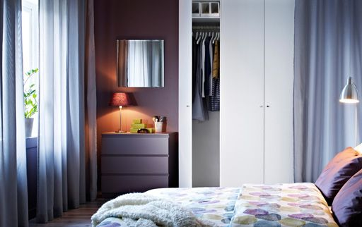 A purple bedroom with purple textiles, a white PAX wardrobe, a white MALM chest of drawers and a KOLJA mirror
