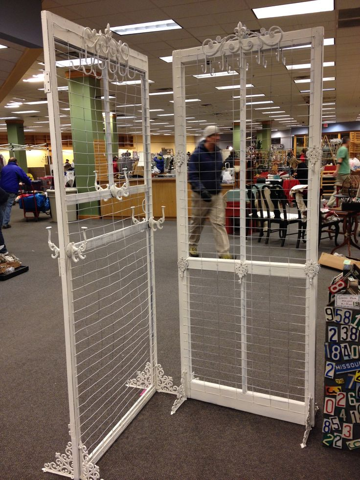 """Salvaged screen doors get a new life as booth display . Rewired the doors with chicken wire, metal brackets on bottom for """"feet"""" so doors are free standing!  Added hooks for added merchandising space. Merchandise both sides of door. JunkChic 5280"""