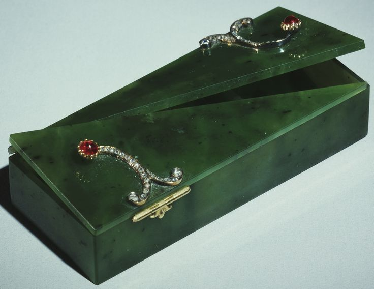 This Fabergé stamp box in nephrite mounted with gold, diamonds and rubies is a good example of a beautifully designed yet practical object, which shows the quality of workmanship and attention to detail which Fabergé paid to all the objects made by his firm, however insignificant and whatever their cost. The top is fitted with two lids which meet diagonally. Inside, the three compartments have sloping bases to enable stamps to be removed easily. Mark of Michael Perchin, 1903.