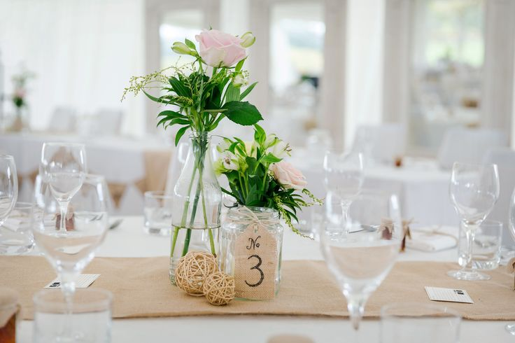Wedding table setup. Jar centrepieces, loose pastel coloured flowers, twine balls, handmade hessian table numbers and table runners.
