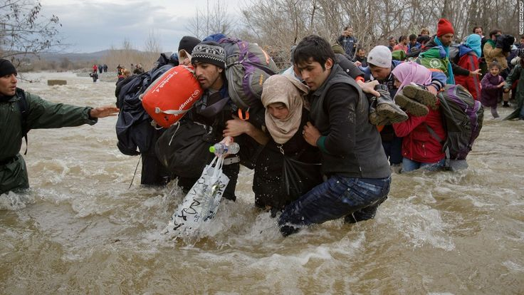 Migrants stumble as they cross a river north of Idomeni, Greece, attempting to reach Macedonia on a route that would bypass the border-control fence on Monday, March 14.