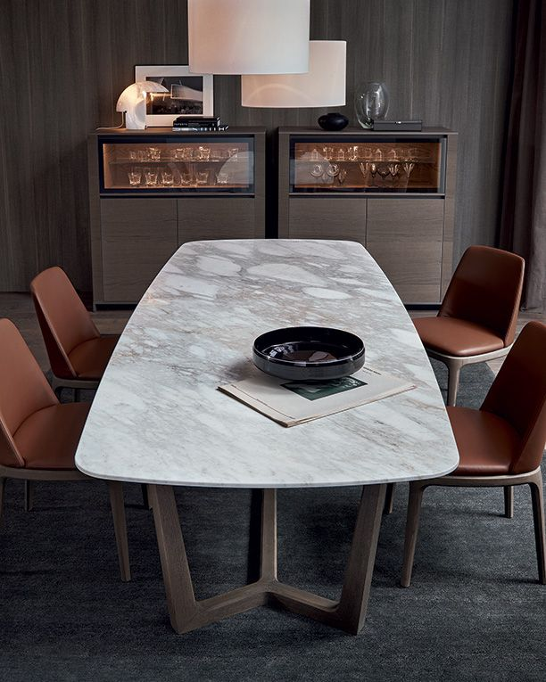 Concorde table with structure in cenere oak, mat calacatta oro marble top. Grace chairs and armchairs with structure in cenere oak, body covered in 48 nocciola Special leather. Febe sideboards in cenere oak with transparent reflecting glass flap door .