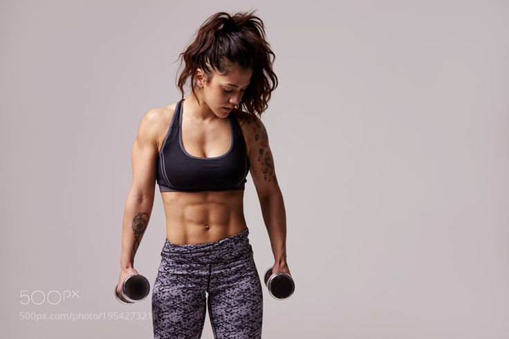 Muscular dark haired young woman working out with dumbbells by GuerillaProductions Muscular dark haired young woman working out with dumbbells