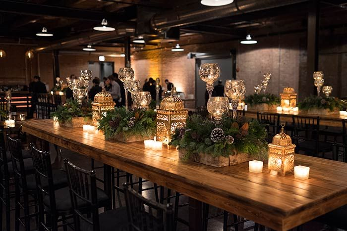 The seasonal greenery also appeared as table decor, along with lanterns and goblet-style votive candlesticks, complementing the rustic vibe of the dining space.  Photo: Eric Rademacher