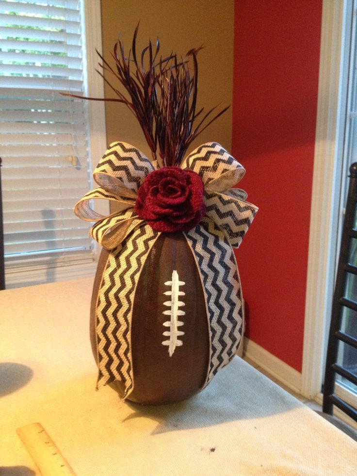 Football pumpkin tailgating table decor with Gamecock feathers