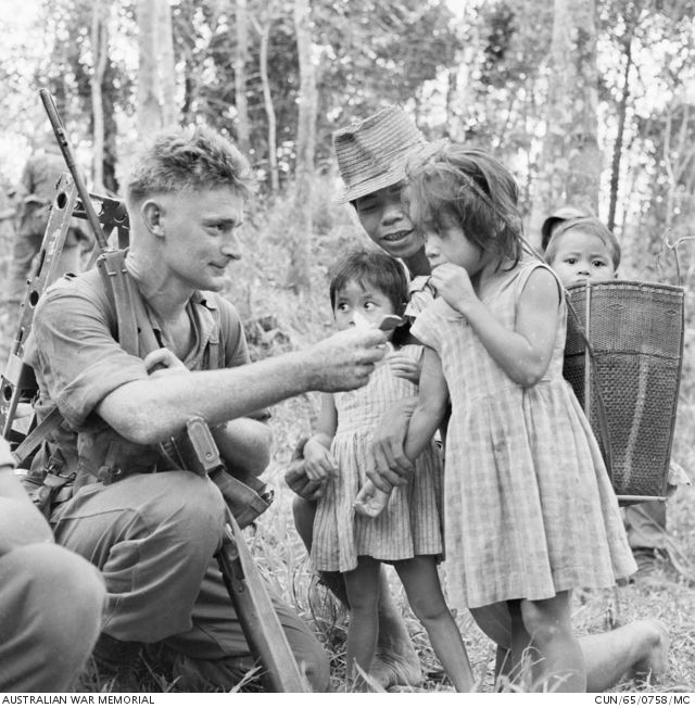 While taking a break from patrolling along the Sarawak-Kalimantan border area in North Borneo, 16364 Private (Pte) Thomas Clarence (Tom) Moores (left), of Rockhampton, Qld, 3rd Battalion, The Royal Australian Regiment (3RAR), hands out his chocholate ration to some local Dyak children. Pte Moores is armed with an L1A1 self loading rifle (SLR), and he is carrying an Alice frame pack.