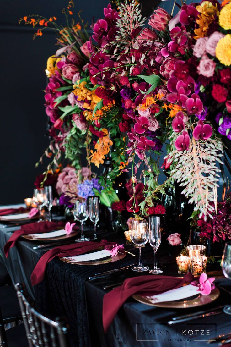 Luxury Bohemian wedding flowers, boho wedding, purple orchids, red orchids, luxury marsala wedding, black candles, black table clothes, gold and black, exotic flowers, luxury wedding.