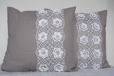 Grey pillows with crochet flower-patterned lace