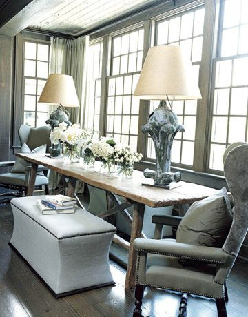 Great long rustic trestle table and curved ottoman benches in a windowed dining alcove