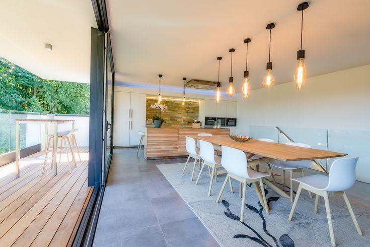 Séjour avec grande baie vitrée à double coulissante ouverte sur terrasse couverte. Maison Dwelling en structure bois massif CLT