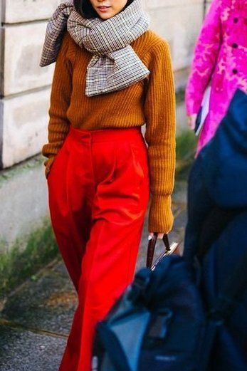 Yoyo Cao accessorizes her bold red pants and mustard yellow knit sweater with a plaid-printed scarf.