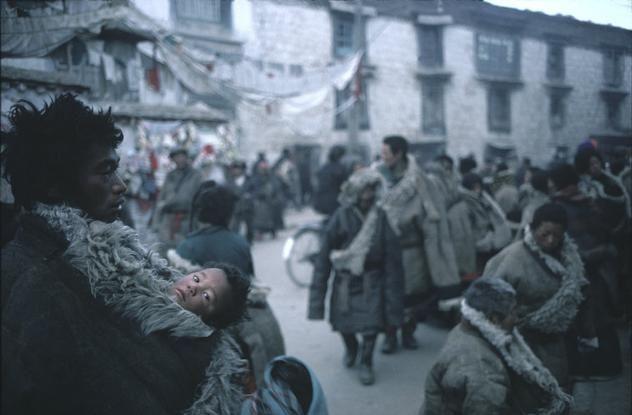Magnum Photos Photographer Portfolio - CHINA. 1981. Lhasa. Tibet. A father carries an almost naked child inside a thick sheepskin overcoat. - Hiroji Kubota