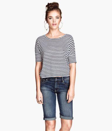 H&M NL &DENIM. Een knielange 5-pocketshort van elastisch, gewassen denim. De short heeft een muntzakje en achterzakken met een ritssluiting en een vastgestikte omslag onder aan de pijpen.