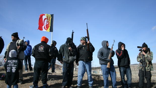 Members of the American Indian Movement stand near the Wounded Knee Massacre Monument, Wednesday, Feb. 27, 2013 in Wounded Knee, S.D. - Hundreds of people walked from nearby villages to the site of the occupation, drumming and chanting. Once at the site, the same place where in 1890 soldiers slaughtered an estimated 300 Native American men, women and children, AIM and their supporters continued to drum and chant and fire off gunshots into the air. Honored Russell Means