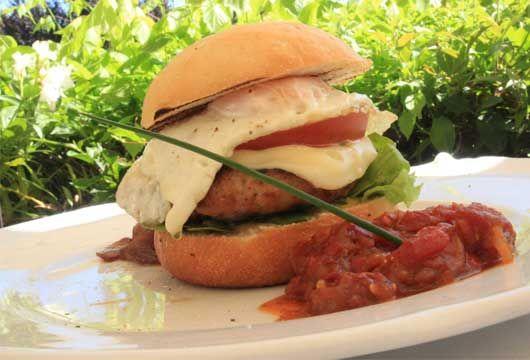 «Burger κοτόπουλο με αυγό, τυρί, σάλτσα μουστάρδας, τσάτνεϊ γλυκοκαυτερής ντομάτας και καραμελωμένες πέρλες κρεμμυδιού» από το Ζύθο
