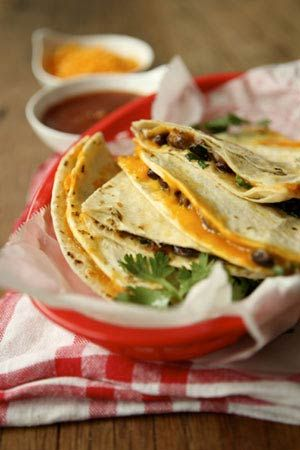 These basic quesadillas come together quickly and adapt well to many variations. Add salsa, sautéed onions or peppers and diced red or white onion, if you like. Serve with a green salad for dinner or alone as a hearty after-school snack.