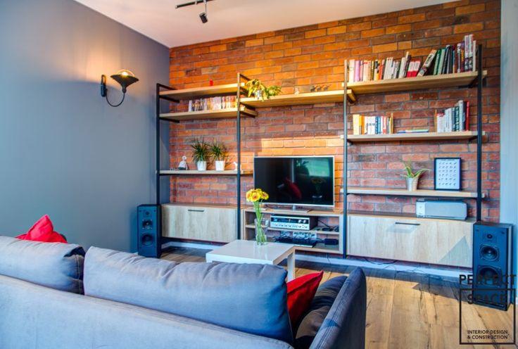 Wnętrze nowoczesnego salonu z ceglaną ścianą, na której umieszczono regał z półkami. Drewniana podłoga, wygodna sofa i ciepłe oświetlenie tworzą domową atmosferę.