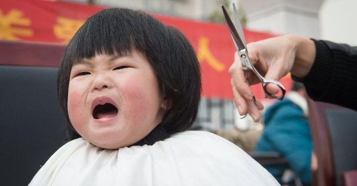 """20150321 - Criança chinesa chora ao receber um corte de cabelo gratuito neste sábado (21). No calendário lunar da China, hoje é o segundo dia do segundo mês do ano, o dia em que o """"dragão mostra a sua cabeça"""". A imagem representa o despertar da natureza na primavera, após a hibernação do inverno. Nesse dia, as pessoas cortam o cabelo para ter boa sorte  PICTURE: Du Yu/Xinhua"""