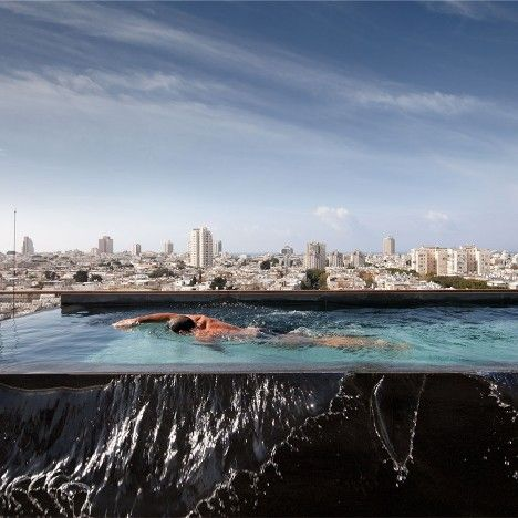 A rooftop swimming pool runs along the edge of this renovated penthouse in Tel Aviv by Israeli architect Pitsou Kedem