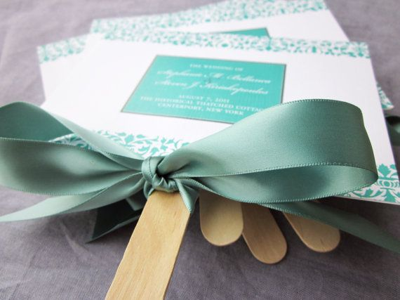 Wedding programs as fans, but with ribbons hanging down, instead of tied in a bow.