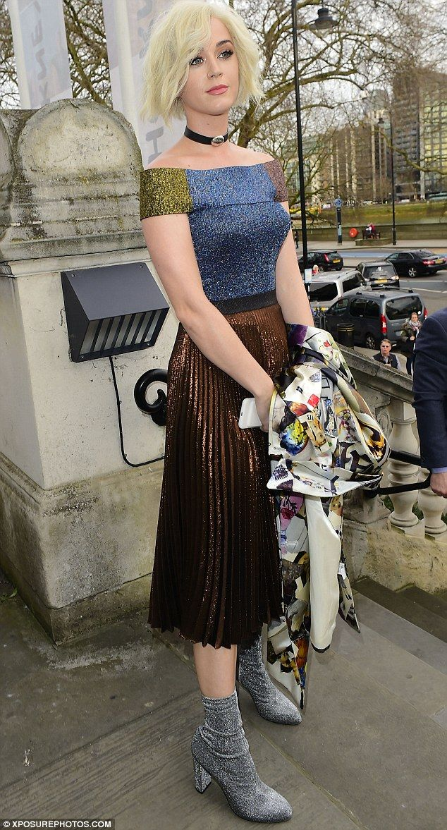 Making a statement: The 32-year-old Firework star arrived at the bash in a kooky patchwork coat before whipping off the garment to show a stunning Bardot top and pleated skirt combo