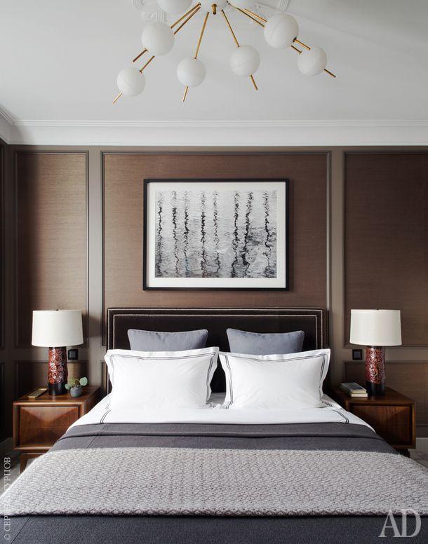 Кровать сделана на заказ и обита бархатом, Kravet. Прикроватные тумбочки винтажные. На стенах обои из натурального волокна, Kneedler|Fauchère. В изголовье фоторабота Яниса Дейнатса. На потолке итальянская винтажная люстра.