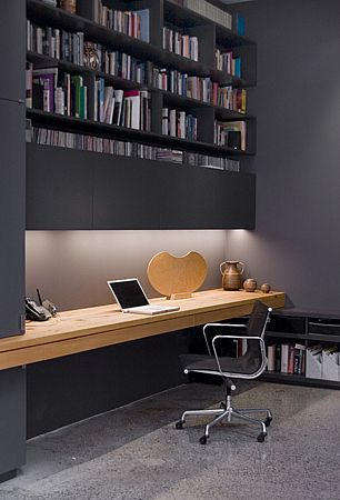 Gorgeous black home office space with big bookshelf.