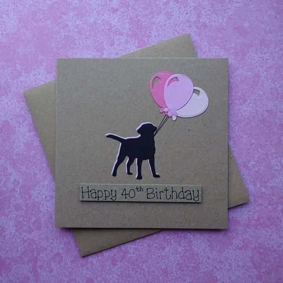 Labrador birthday card with a black Labrador holding a bunch of birthday balloons.  This handmade birthday balloons card has a silhouette of a Labrador (Black Lab) standing happily, holding the strings to a bunch of balloons. The sentiment on this handmade birthday card is added with 3D foam and reads: Have a paw-some birthday! PERSONALISING YOUR CARD: You can choose the colour of the balloons and matching dog shadow on this happy birthday card from the drop-down menu. If you choose a…