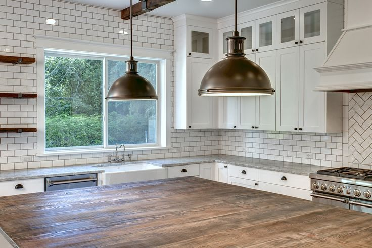 The grand island, wooden ceiling beams and wooden shelves. Along with the white back splash and Thermidor refrigerator and freezer. By American Classic Homes.