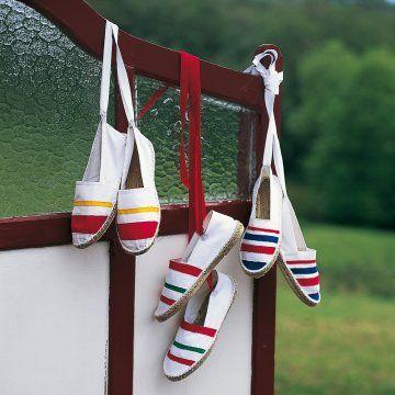 des espadrilles blanches avec des rubans pour les attacher aux chevilles et des rayures peintes puis rebrodées rouge, vert, jaune, bleu comme au pays basque