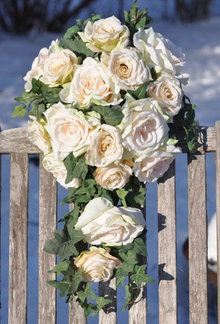 Thisa cascade bouquet is made with champagne roses and blush peach roses with frosted ivy that are silk flowers in a cascading bouquet shape.
