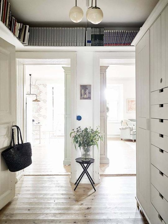Here's a clever idea spotted on Keltainen Talo Rannalla: mount a shelf on the wall, above the door frames, to provide a little extra storage in a hallway.