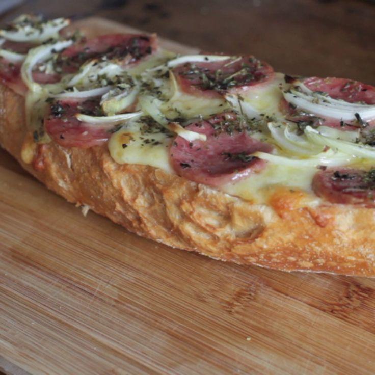 Receita com instruções em vídeo: Essa pizza no pão é deliciosa e vai te salvar sempre! Ingredientes: 1 baguete, 1/2 xícara de molho de tomate, Sal, 200g de muzzarela ralada, 200g de calabresa, 1 cebola, Azeite de oliva, Óregano