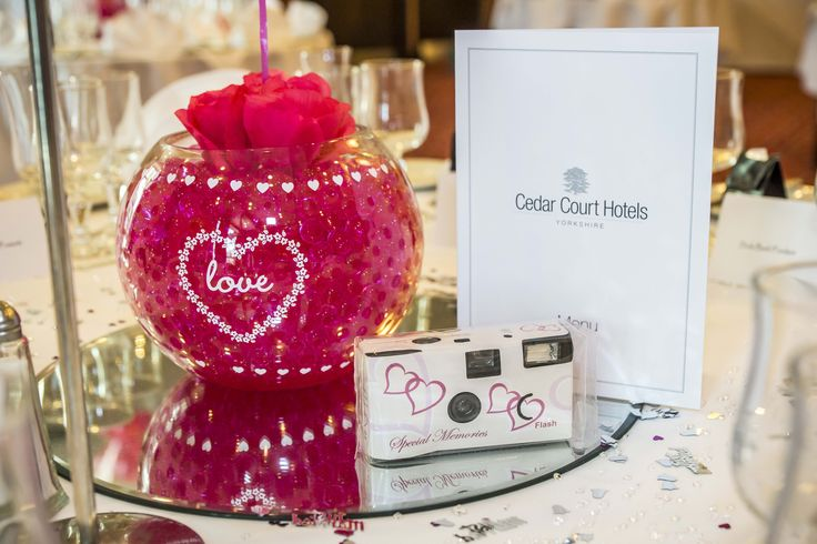 Fish bowl filled with pink flowers and pink see through stones, with a camera for your guests to capture every moment.