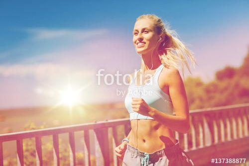 """Laden Sie das lizenzfreie Foto """"smiling young woman running outdoors"""" von Syda Productions zum günstigen Preis auf Fotolia.com herunter. Stöbern Sie in unserer Bilddatenbank und finden Sie schnell das perfekte Stockfoto für Ihr Marketing-Projekt!"""