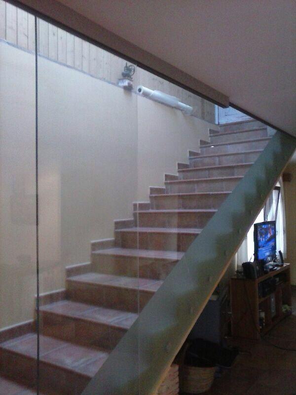 pared de cristal templado para cerrar el hueco de la escalera instalado mediante soportes inferiores