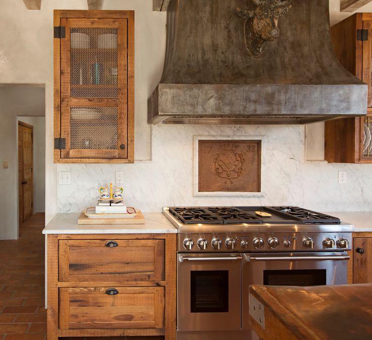 Дизайн кухни в деревенском стиле: фамильный герб над плитой
