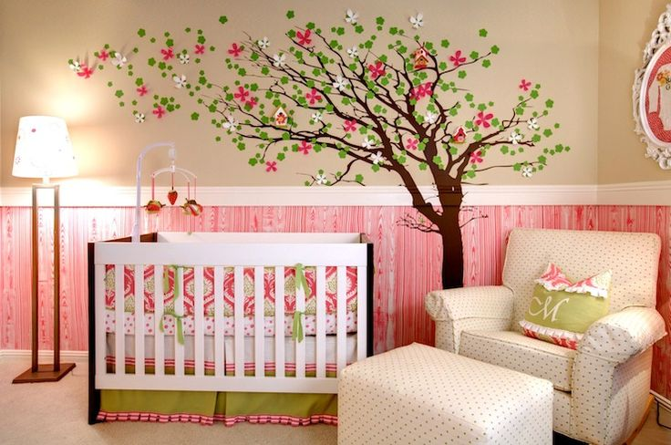 Sweet girl's pink and green nursery design with tan paint paired with pink faux bois wallpaper. Adorable tree stencil with pink and green flower appliques frame white crib with pink and green crib bedding. Ikea Ung Drill over rolled-arm glider and matching ottoman is the perfect spot to nurse baby.