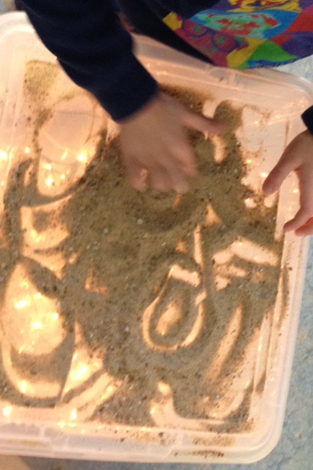 Tekenen in zand (Plastieken bak met kerstlampjes in/lichtbak) Inleiding; zandtovenaar filmpje -- de kleuters vinden dit geweldig