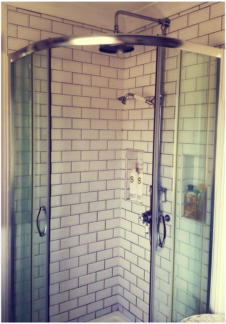 Brick tiled shower, using grey grout, with large rain shower head. Built in wall storage.