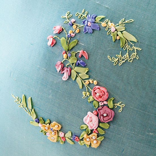 A teal pillow beautifully showcases a chromatic cascade of diverse flower shapes that form the S. Pink and mauve stitched roses highlight the center of the letter. Bell-shape and multiple-petal blooms in pink, blue, and mauve ribbon follow the letter's curves. Petite buds, rendered with French knots, line up along embroidered stems sprouting ribbon-stitched leaves.