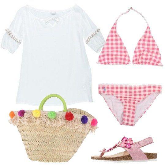 Abbigliamento da spiaggia, per una piccola diva: bikini Ralph Lauren, fantasia Vichy rosa e bianca, copricostume bianco con laccetti al collo e ricami sulle maniche, infradito in tessuto con applicazioni a forma di cuore, borsa di paglia con pompon colorati.