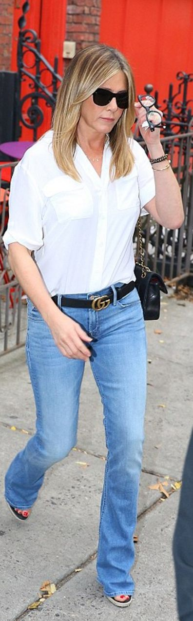 Who made  Jennifer Aniston's black sunglasses, white button down shirt, gold jewelry, quilted handbag, wedge sandals, and blue flared jeans?
