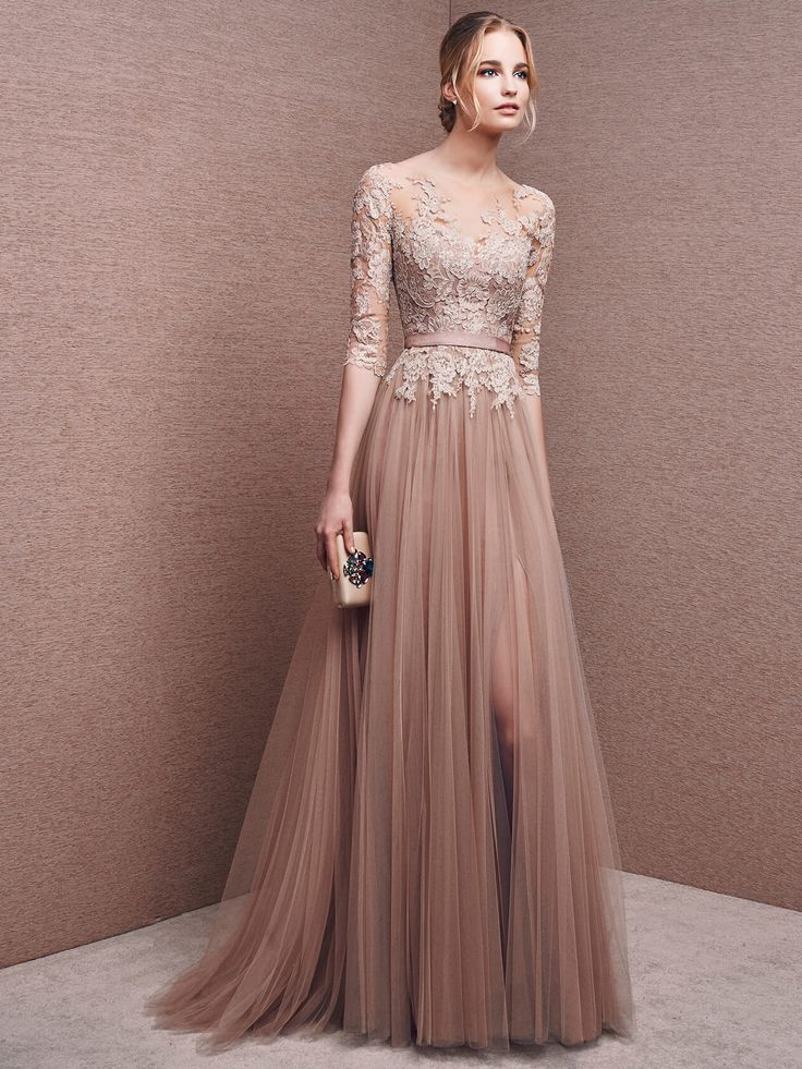 Элегантное вечернее платье темного кремового цвета обрисовывает силуэт прямым кроем, выразительно воплощенным в шифоне, множеством вертикальных складок ниспадающим от линии талии. Выделить ее помогает узкий атласный пояс. Верх платья покрыт полупрозрачной вставкой, скрывающей декольте и образующей длинные облегающие рукава. По всей длине она декорирована кружевными аппликациями нежного бежевого оттенка. Вечернее платье 2016 года